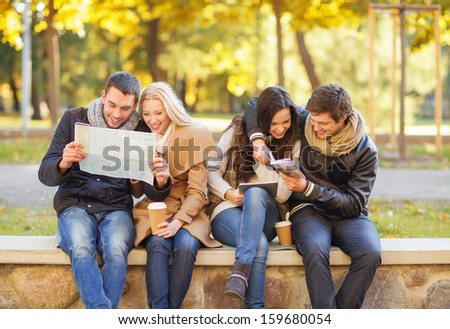 holidays and tourism, navigation concept - group of friends or couples with tourist map and tablet pc computer in autumn park