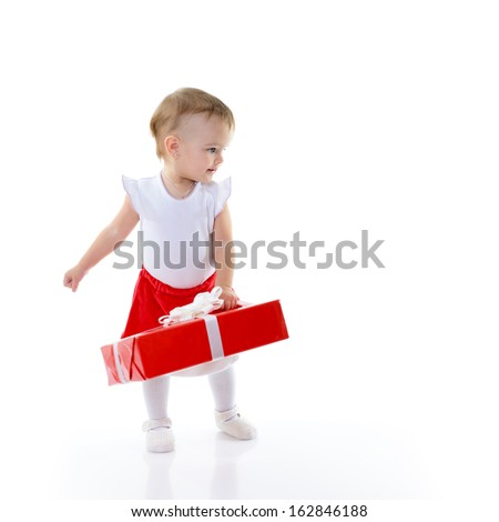 Holidays, baby girl holding a present and looking rigth at copyspace, christmas, birthday, new year, x-mas concept - happy child girl with gift boxes  - stock photo