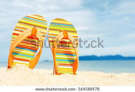 Holidays Background. Beach sandals on the sandy coast - stock photo