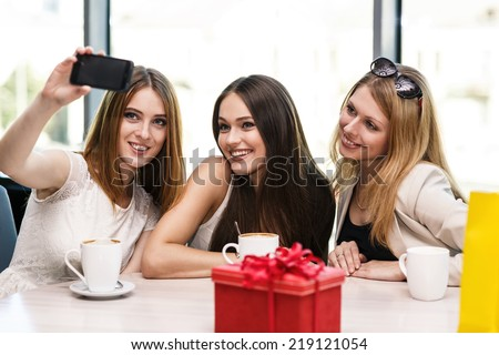 Holidays - beautiful girls taking picture in cafe - stock photo