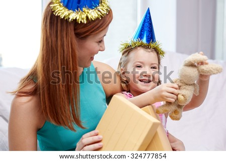 holidays, birthday, family, childhood and people concept - happy mother and little girl in party caps with gift box and toy at home - stock photo