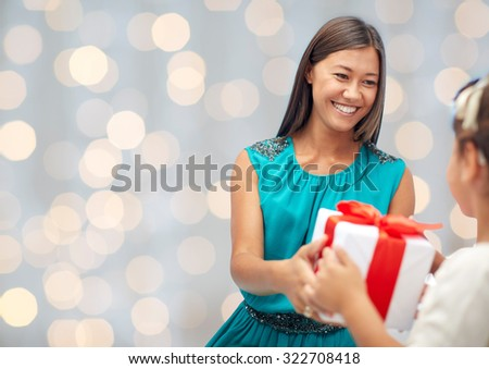 holidays, birthday family, childhood and people concept - happy mother giving present to her daughter rover holidays lights background - stock photo