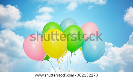 holidays, birthday, party and decoration concept - bunch of inflated colorful helium balloons over blue sky and clouds background - stock photo