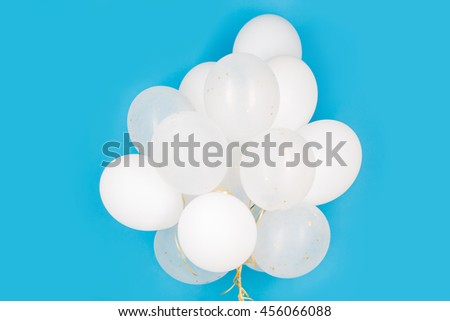 holidays, birthday, party and decoration concept - close up of inflated white helium balloons over blue background - stock photo