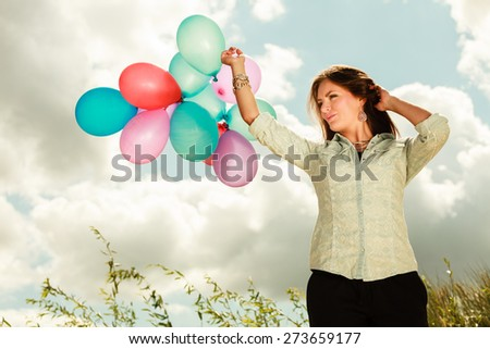 holidays, celebration and lifestyle concept - attractive woman female model holding bunch of colorful balloons outside cloudy sky background