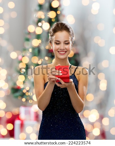 holidays, celebration and people concept - smiling woman in dress holding red gift box over christmas tree lights background - stock photo