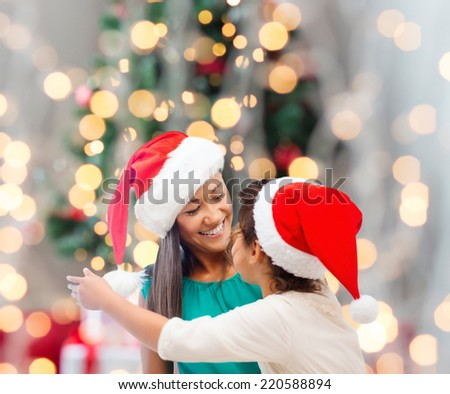 holidays, celebration, family and people concept - happy mother and little girl in santa helper hats over living room and christmas tree background