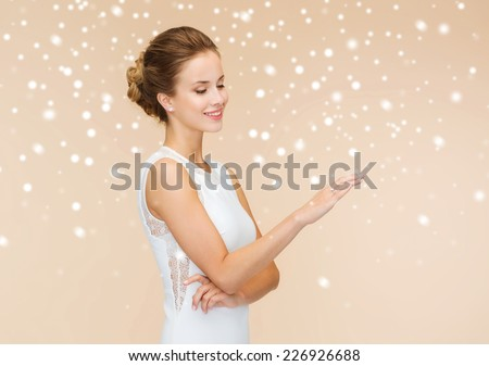 holidays, celebration, wedding and people concept - smiling woman in white dress wearing diamond ring over beige background and snow - stock photo