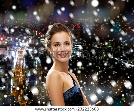 holidays, christmas and people concept - smiling woman in evening dress over snowy night city background