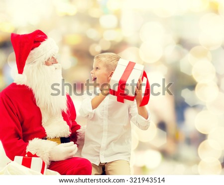 holidays, christmas, childhood and people concept - smiling little boy with santa claus and gifts over lights background - stock photo