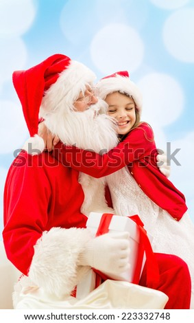 holidays, christmas, childhood and people concept - smiling little girl hugging with santa claus over blue lights background