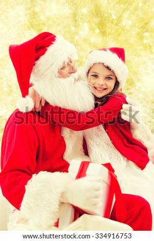 holidays, christmas, childhood and people concept - smiling little girl hugging with santa claus over yellow lights background