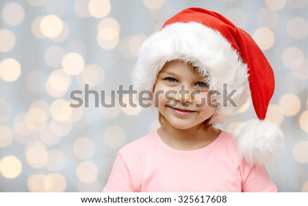 holidays, christmas, childhood and people concept - smiling little girl in santa hat over lights background