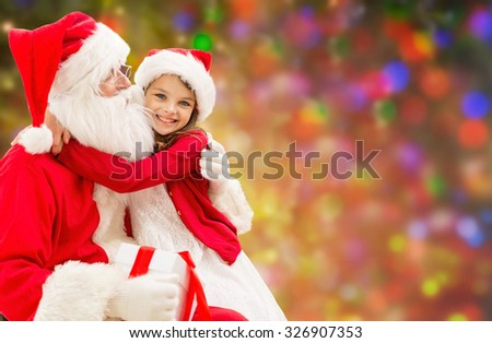 holidays, christmas, happiness and people concept - smiling girl cuddling with santa claus over holidays lights background