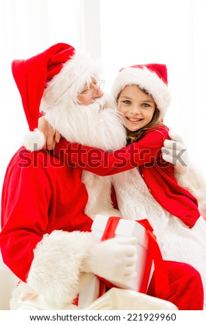 holidays, christmas, happiness and people concept - smiling girl with gift box embracing santa claus at home - stock photo
