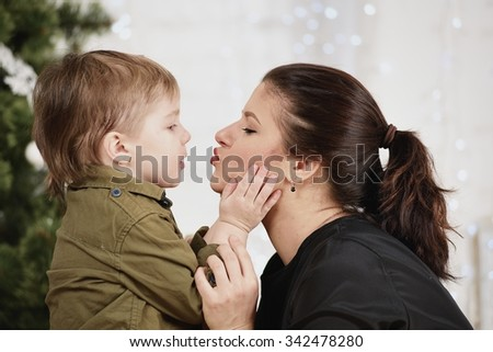 Holidays, christmas, love and happy family. Little boy kissing mother - stock photo