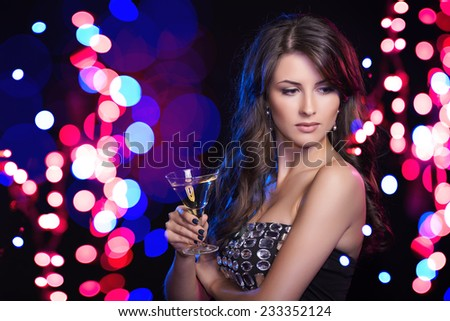 Holidays, christmas, people celebration concept. Clsoseup of sensual woman in evening dress with glass over holidays lights bokeh background