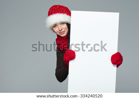 Holidays, Christmas. Portrait of smiling woman wearing Santa hat showing whiteboard banner over gray background - stock photo
