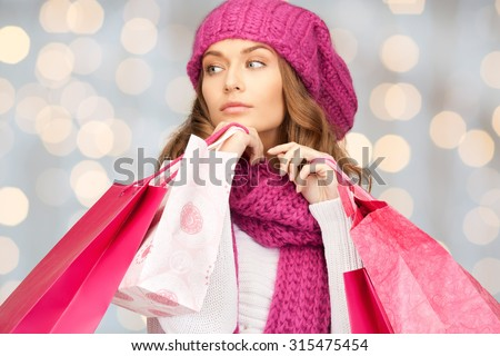 holidays, christmas, sale and people concept - young woman in winter clothes with shopping bags over lights background - stock photo