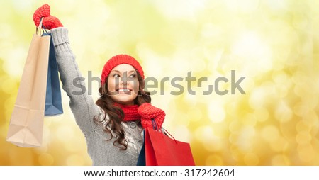 holidays, christmas, x-mas, sale and people concept - happy young asian woman in winter clothes with shopping bags over yellow lights background - stock photo