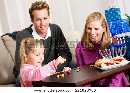 Holidays: Family Plays Hanukkah Dreidel Game Together - stock photo