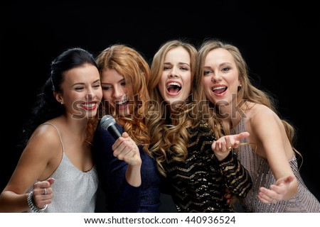 holidays, friends, bachelor party, nightlife and people concept - three women in evening dresses with microphone singing karaoke over black background - stock photo