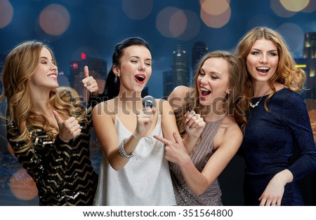 holidays, friends, bachelorette party, nightlife and people concept - three women in evening dresses with microphone singing karaoke over city and lights background - stock photo