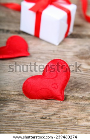 Holidays gift and red heart on wooden background. Valentines day background.
