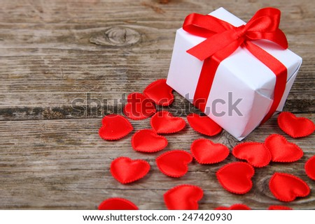 Holidays gift and red hearts on wooden background. Valentines day background. - stock photo