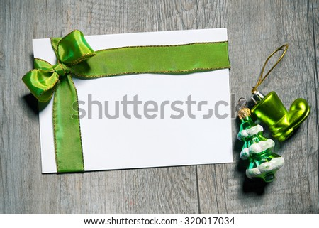 Holidays gift card with green bow on wooden background - stock photo