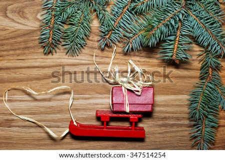 Holidays, gifts, new year, a sled and Christmas tree on the wooden background - stock photo