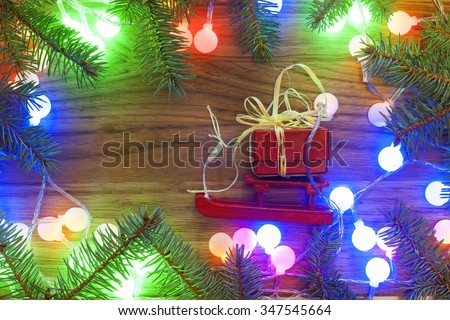 Holidays, gifts, New Year, Snow, Christmas tree with Christmas lights on the wooden background - stock photo
