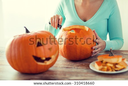 holidays, halloween, decoration and people concept - close up of woman with pumpkins at home - stock photo