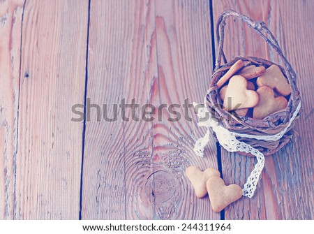 Holidays, love, food and drink concept. Handmade heart cookies for Valentine's day in a basket on a wooden table. Vintage style, toned image. Selective focus, copy space background. - stock photo