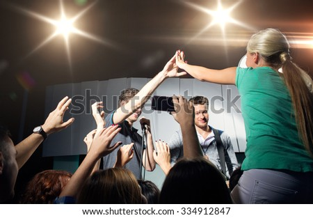 holidays, music, gesture, nightlife and people concept - close up of woman fan making high five with singer at concert in night club