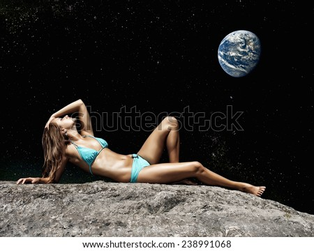 Holidays on the Moon. Woman lying on the ground in the night sky with the Earth. Elements of this image furnished by NASA. - stock photo