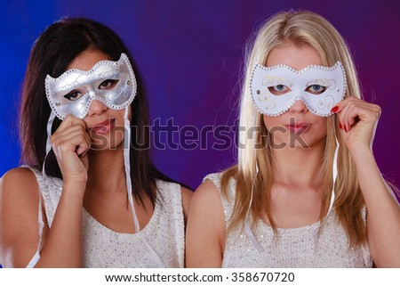 Holidays, people and celebration concept. Closeup two women face african and caucasian with white silver carnival masks