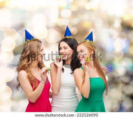 holidays, people and celebration concept - smiling women in party caps blowing to whistles over lights background - stock photo