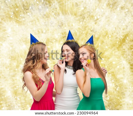 holidays, people and celebration concept - smiling women in party caps blowing to whistles over yellow lights background - stock photo