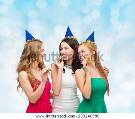 holidays, people and celebration concept - smiling women in party caps blowing to whistles over blue lights background - stock photo