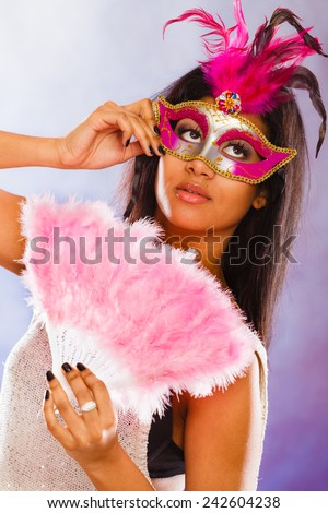 Holidays, people and celebration concept. woman mixed race with carnival venetian masks holding feather fan in hand over festive background.