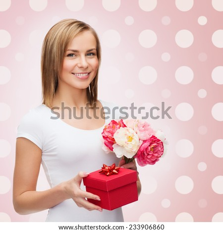 holidays, people and happiness concept - smiling young woman with gift box and flowers over pink white polka dots pattern background - stock photo
