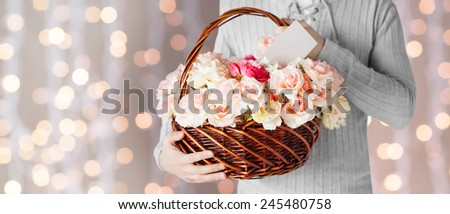 holidays, people, feelings and greetings concept - close up of man holding basket full of flowers and postcard over holidays lights background - stock photo