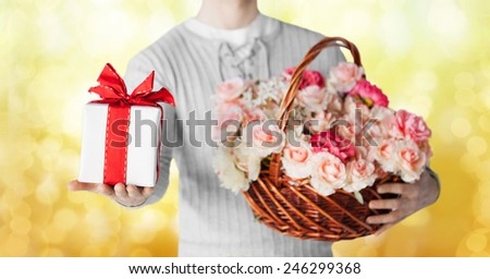 holidays, people, feelings and greetings concept - close up of man holding basket full of flowers and gift box over yellow lights background - stock photo