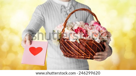 holidays, people, feelings and greetings concept - close up of man holding basket full of flowers and giving postcard over yellow lights background - stock photo