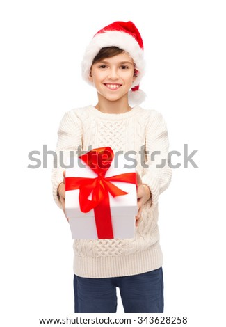 holidays, presents, christmas, childhood and people concept - smiling happy boy in santa hat with gift box - stock photo