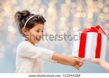 holidays, presents, christmas, childhood and people concept - smiling little girl with gift box over lights background