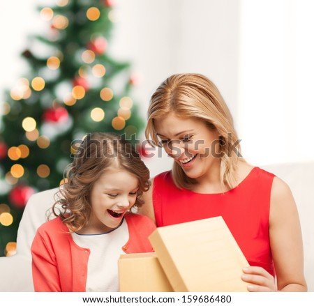 holidays, presents, christmas, x-mas, birthday concept - happy mother and child girl with gift box - stock photo