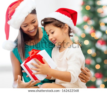 holidays, presents, christmas, x-mas concept - happy mother and child girl in santa helper hats with gift box - stock photo