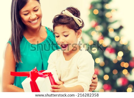 holidays, presents, christmas, x-mas concept - happy mother and child girl with gift box - stock photo